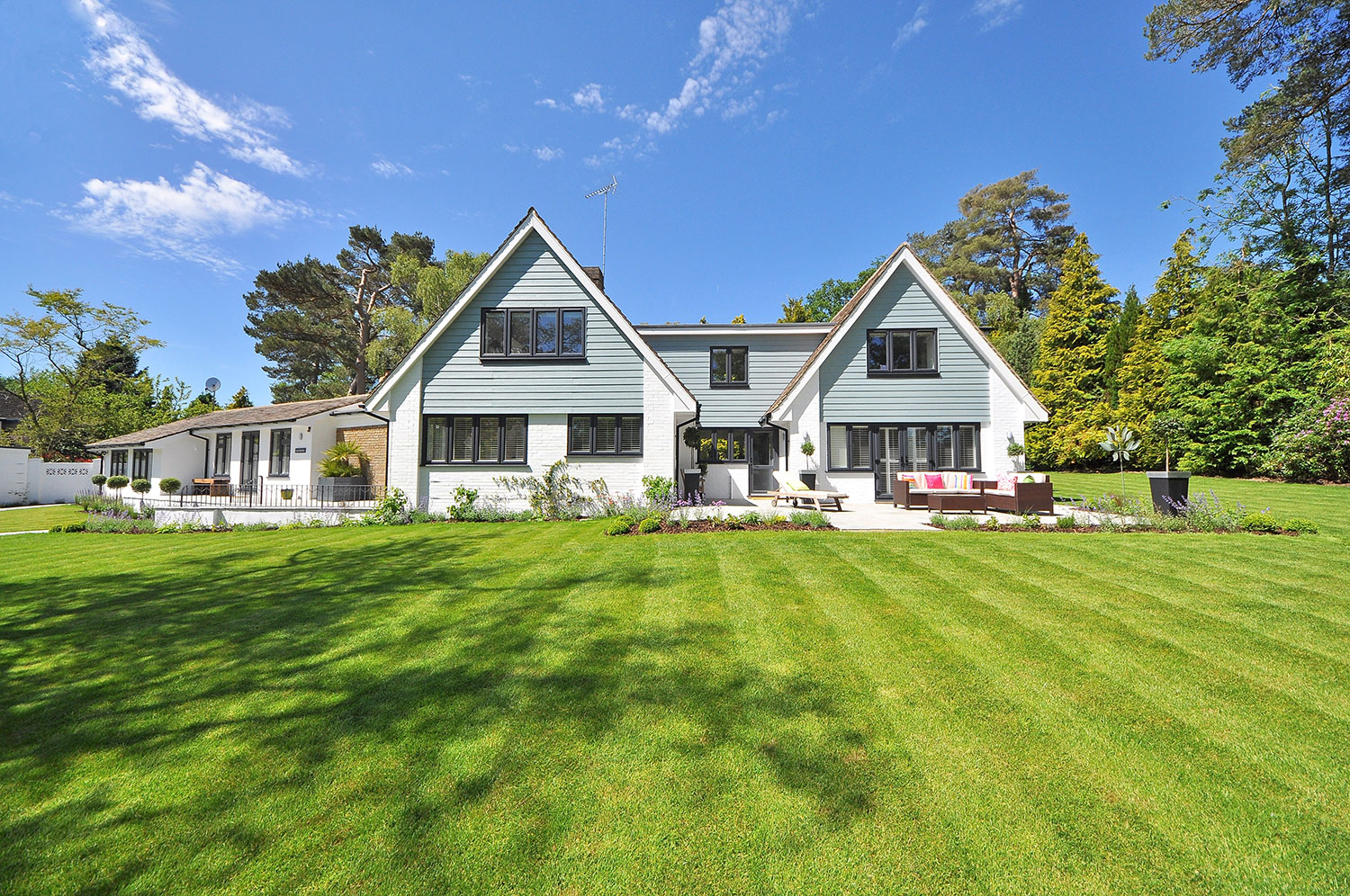 Detached white house with large, well-maintained yard.