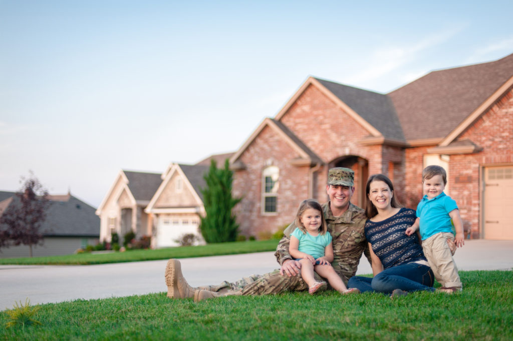 Military veteran and his family sitting on the front lawn outside their home