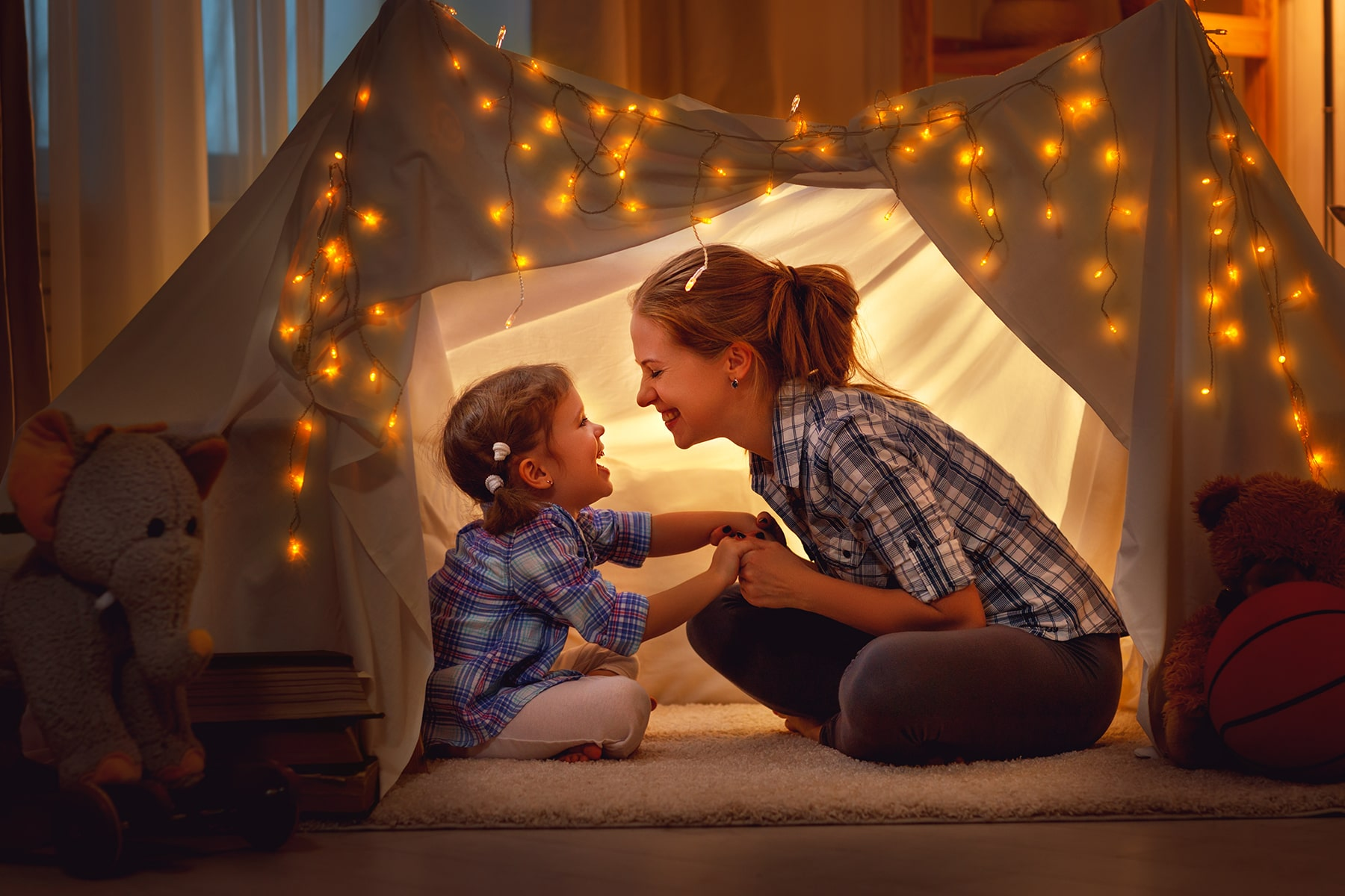 Mother and son playing inside a makeshift tent in their home.